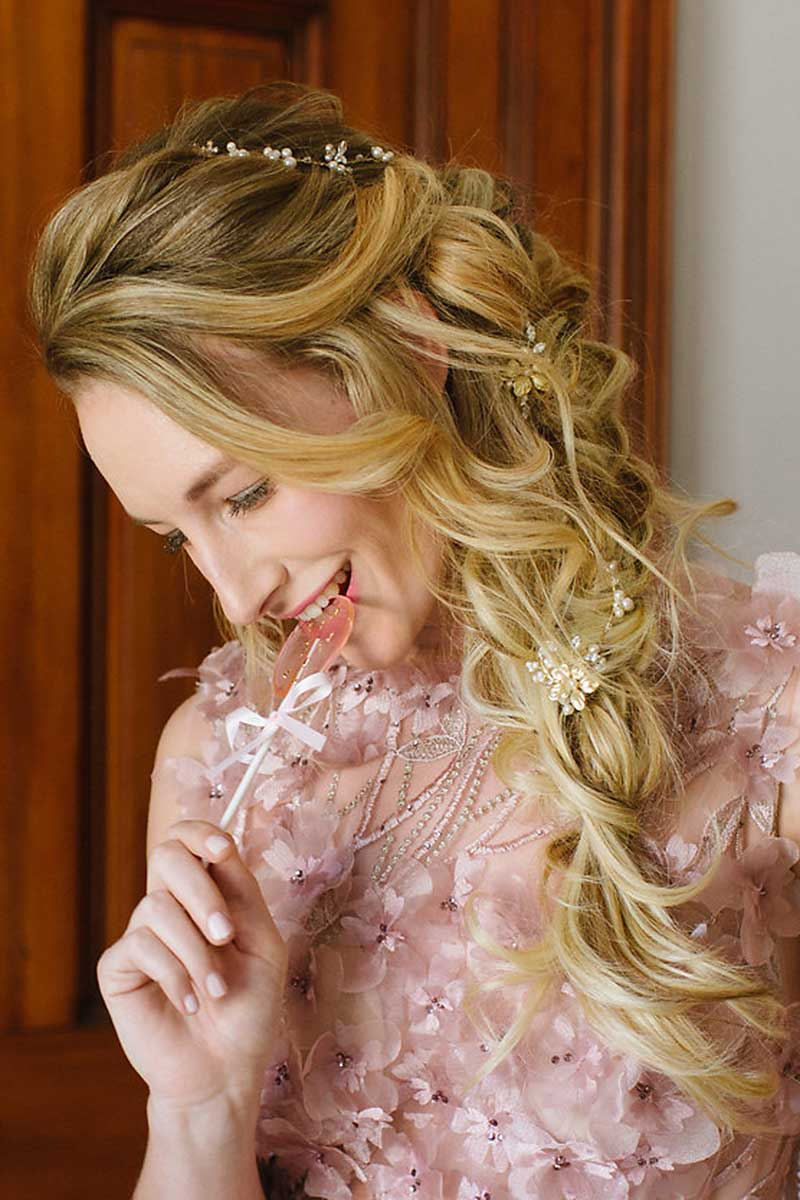Profile of woman holding lollipop wearing Marisol hairvine and hairpins in side braid
