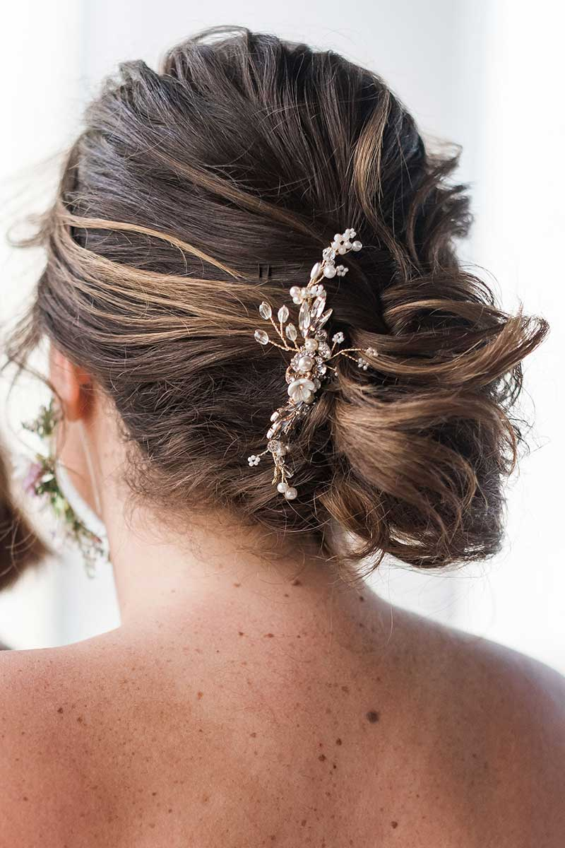 Head and shoulders of woman with messy bun updo and profile gold headpiece