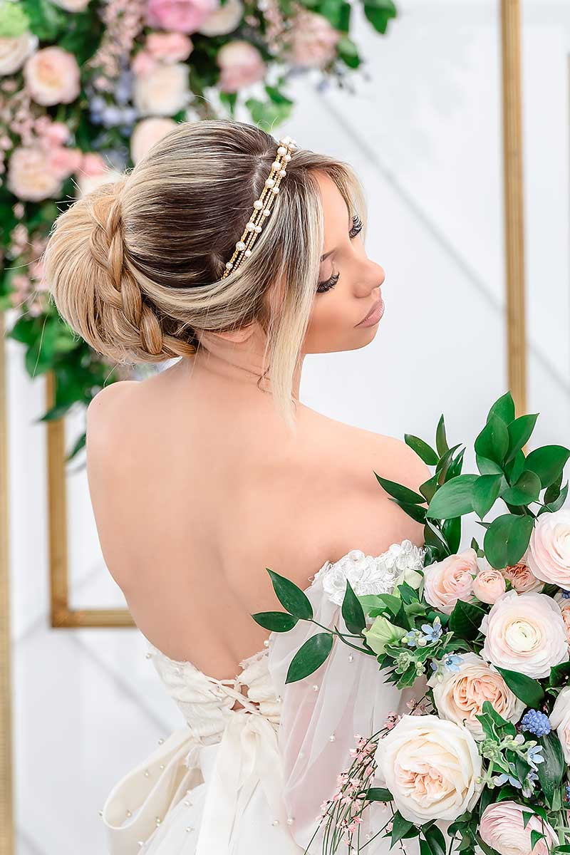 profile of bride wearing Laura Jayne gold pearl crystal stacked headbands holding bouquet of flowersing