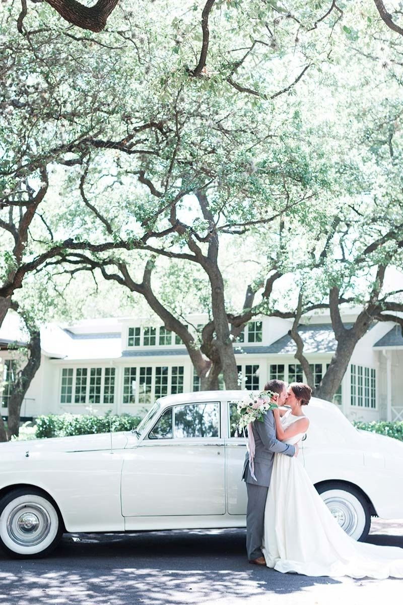 wedding couple standing besides white bently car