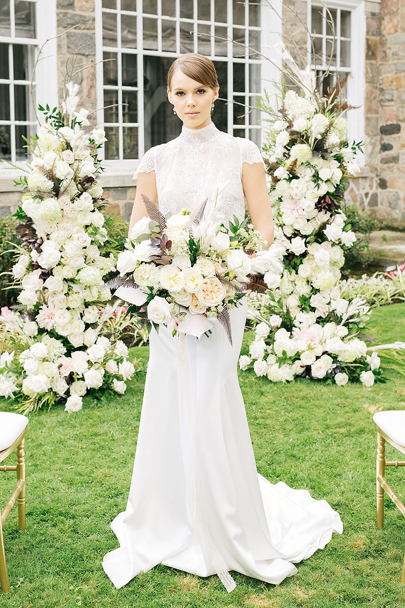 Bride standing outside at floral arch