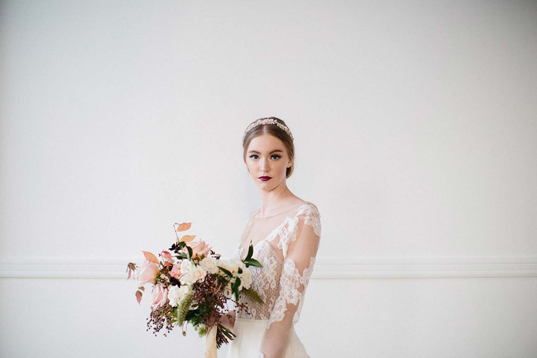 bride wearing a headpiece and holding a bouquet