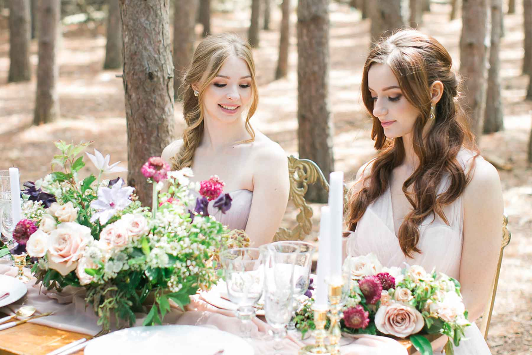 two brides maids sitting at the table with flowers and candles in the nature