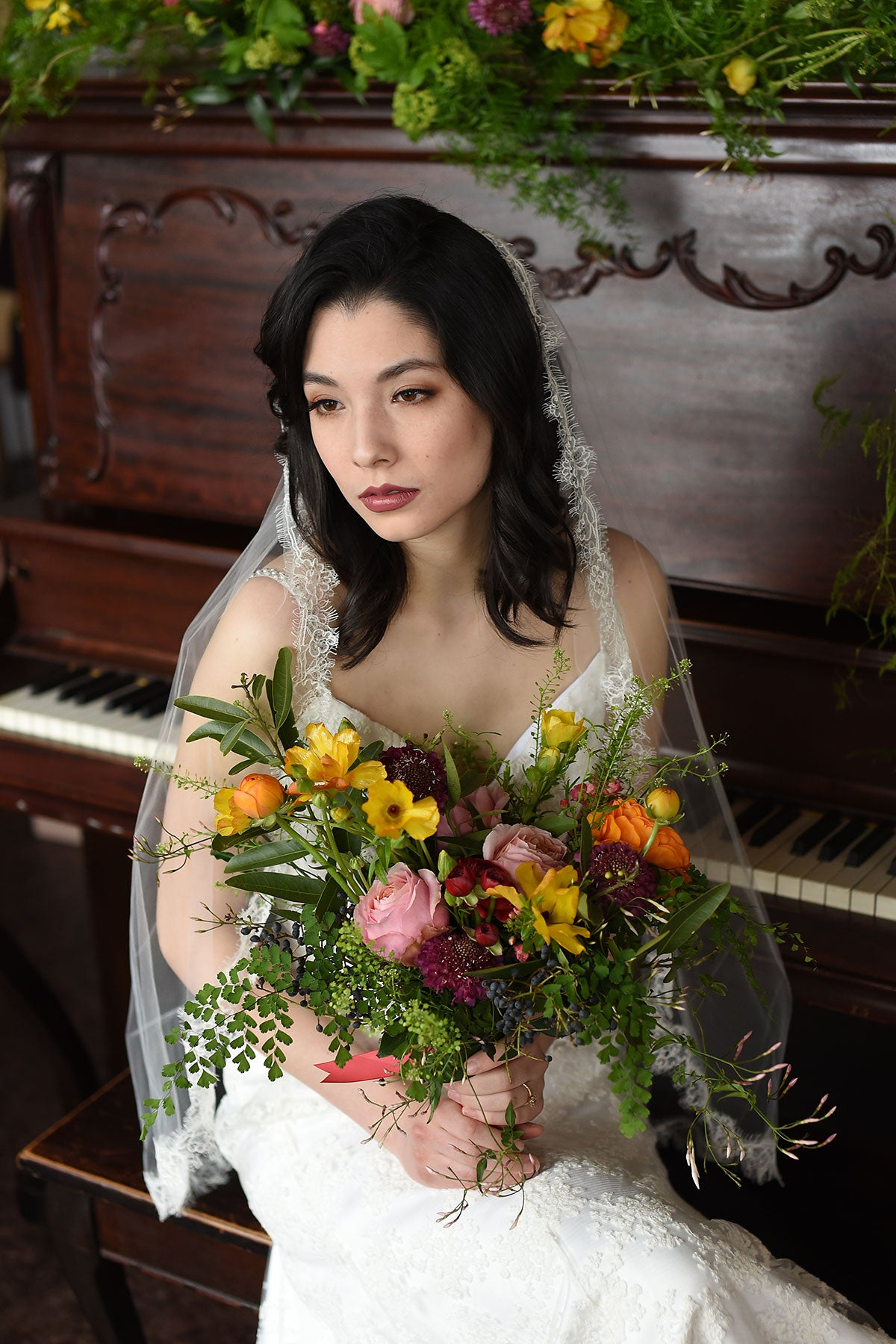bride wearing lace veil and holding a flower bouquet