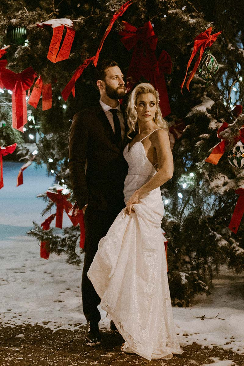 happy bride and groom standing under Christmas tree outdoors