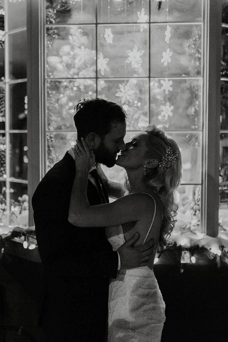 bride and groom kissing on black and white photo