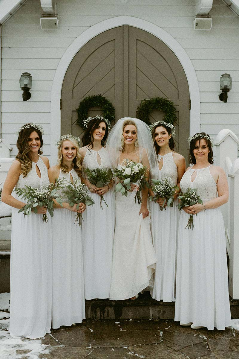 happy bride with bridesmaids holding flower bouquets