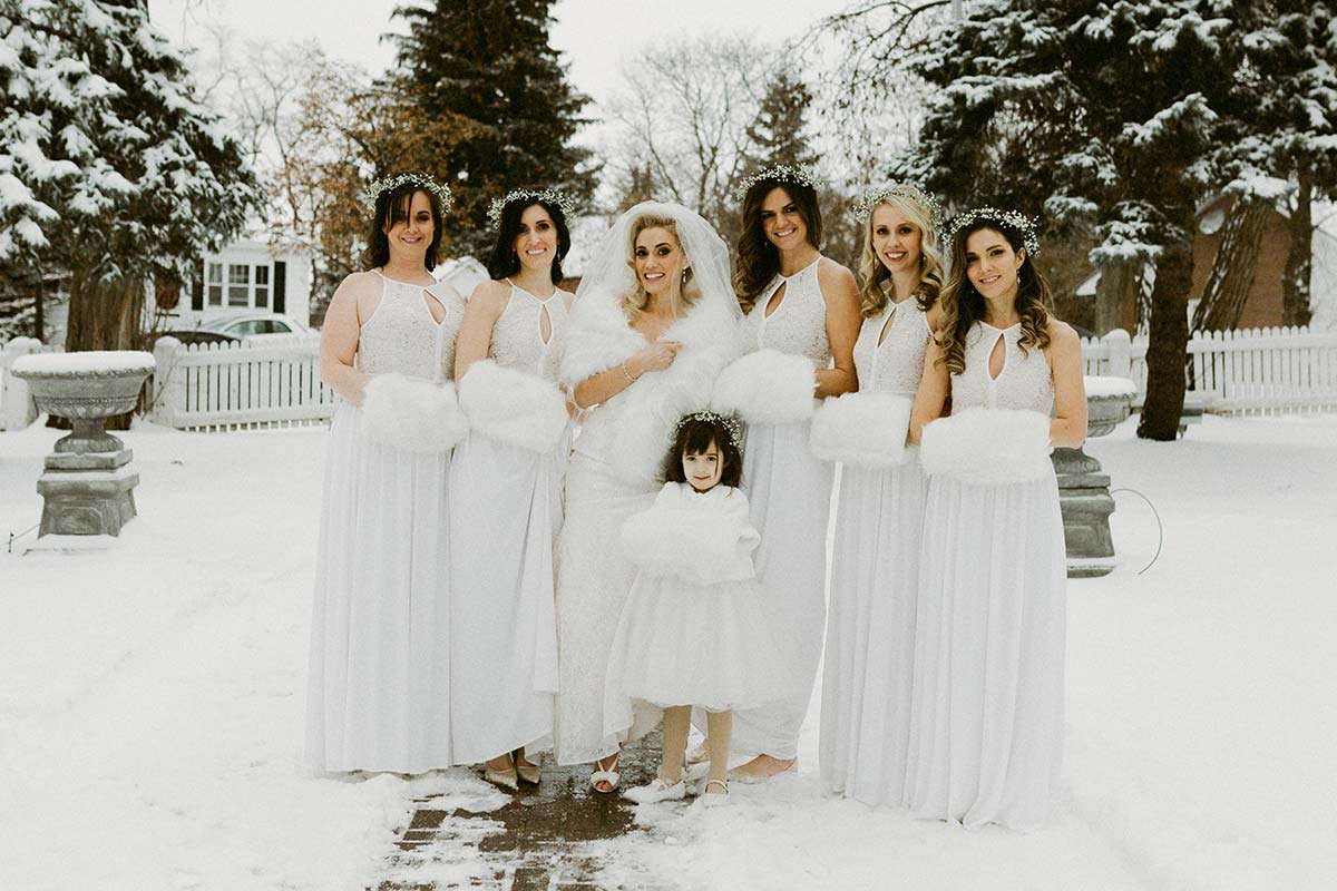 happy bride in feathers and bridesmaids outdoors at a winter wedding