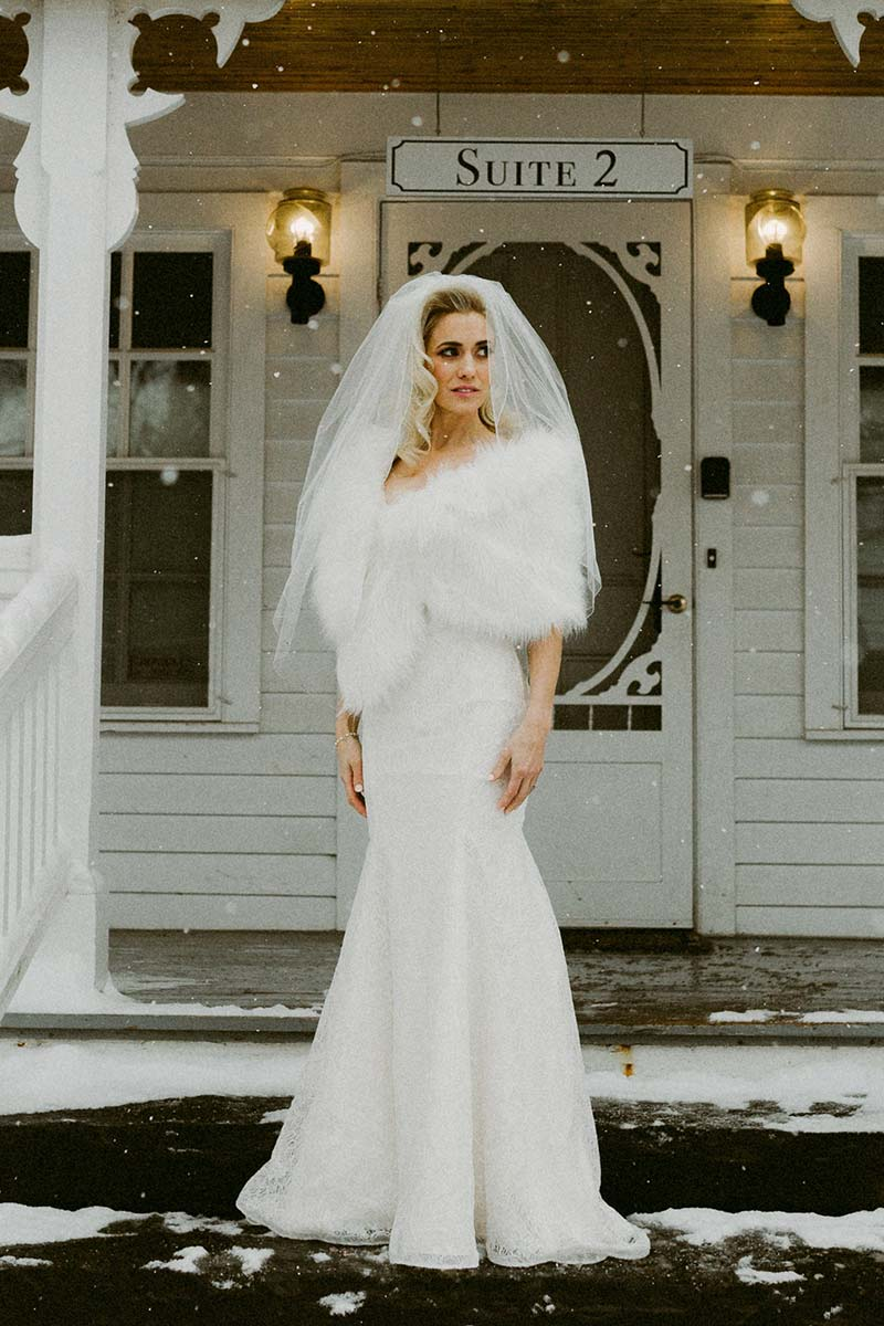 beautiful bride wearing veil and feathers at a winter wedding