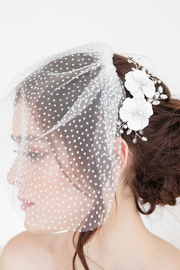 Profile of bride wearing Laura Jayne floral hair comb and dot face veil.