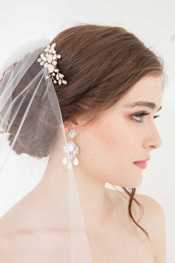 Rose gold crystal profile wedding hair comb on woman with statement drop earrings and veil