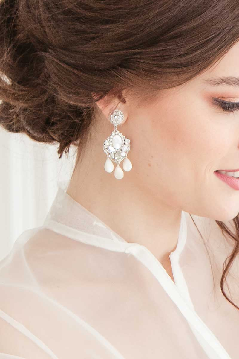 Woman wearing statement crystal earrings with faceted mother of pearl drops.