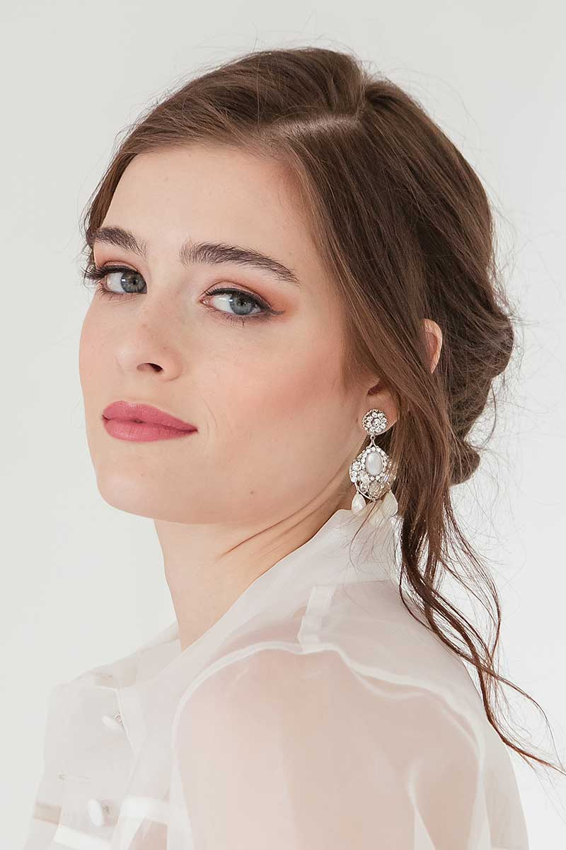 Woman wearing statement filigree crystal mother of pearl earrings