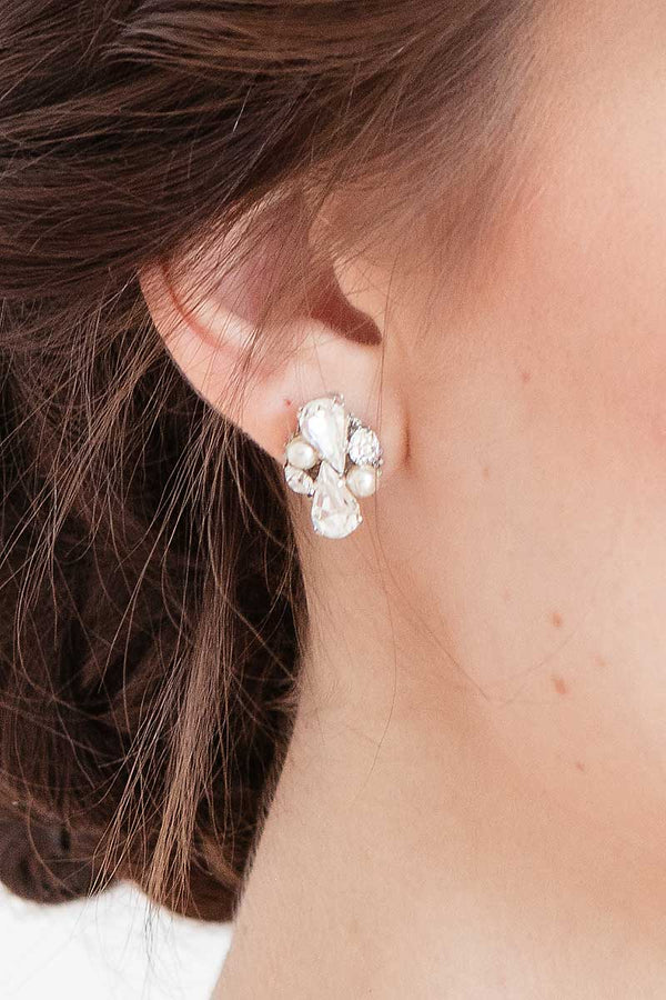 Close up of woman wearing pearl crystal post earring with pear focal stones.