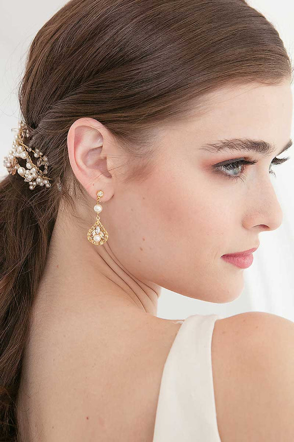Profile of woman wearing pearl gold and champagne crystal bridal earrings.