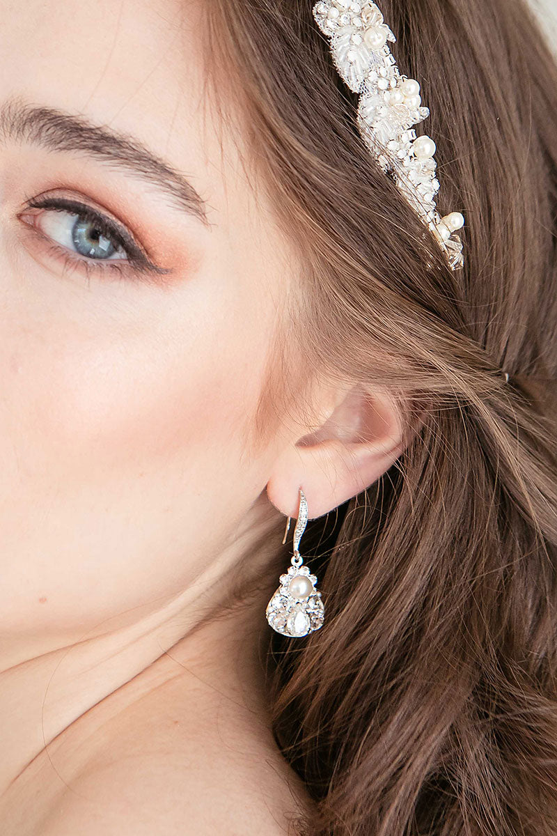 Partial facial view of woman with pearl crystal teardrop earring