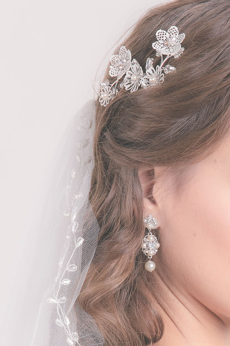 woman wearing haircomb and pearl drop earring