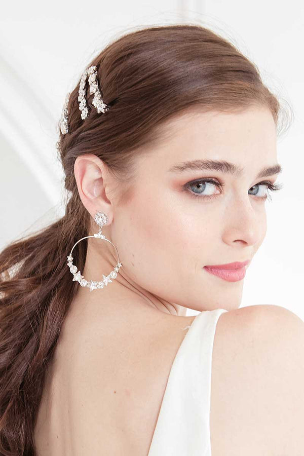 woman with hoop earrings with stars and crystal barrettes