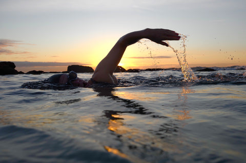 Swimmer pushing arm out of water at sunrise