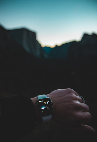 Photo of arm with watch with sunrise in background