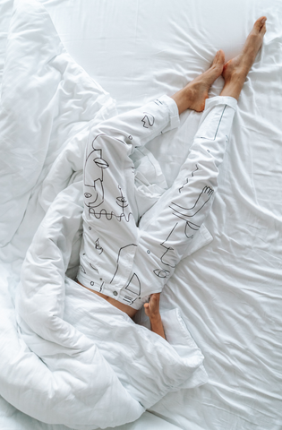 Woman laying in bed with cover over face