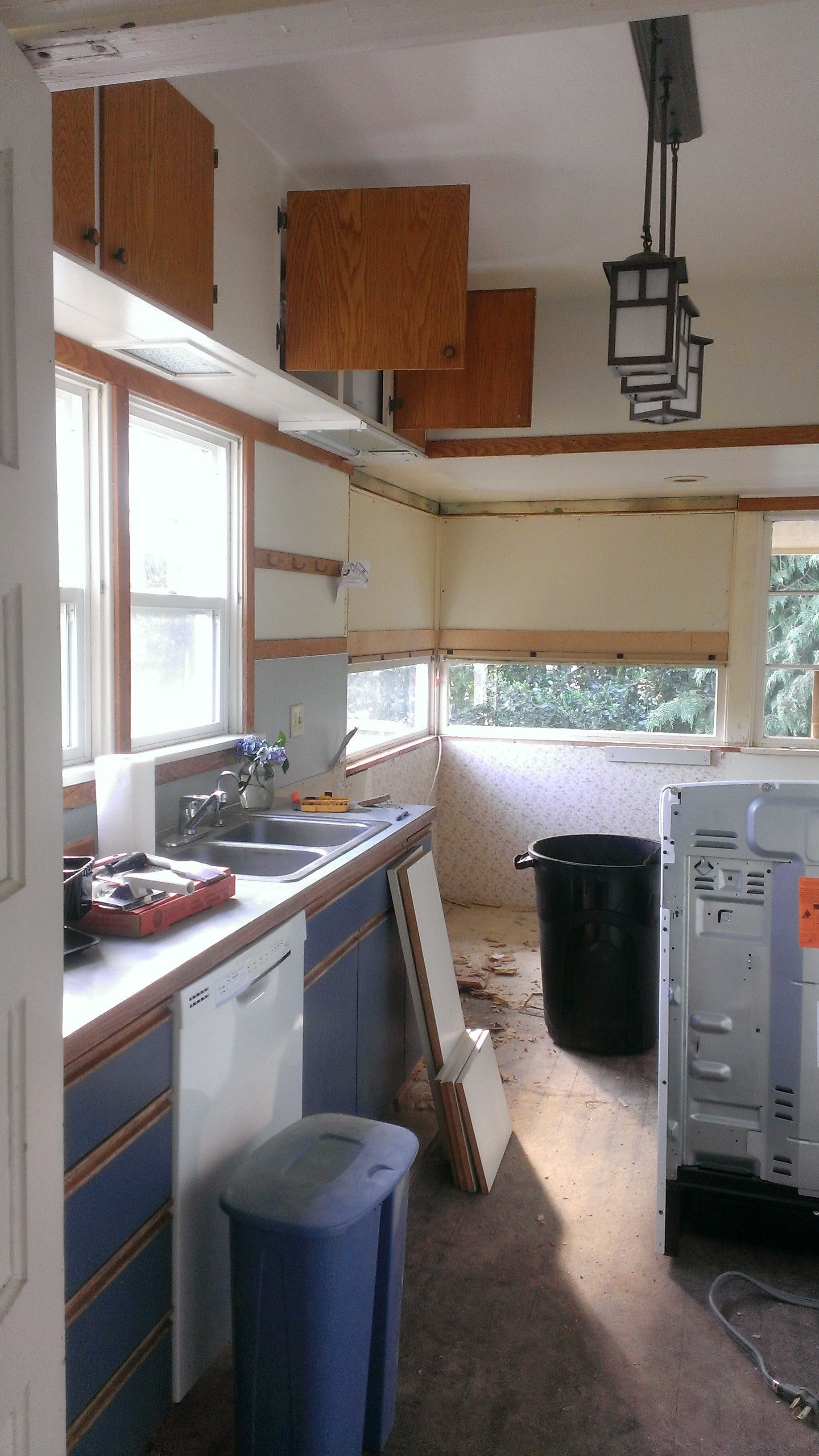 The kitchen when we moved in had two soffits (lowered areas of ceiling), old cabinets and old wood windows that had been covered up to place upper cabinets over the top of them