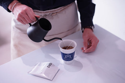 Pouring hot water over a Philocoffea 013 Rudder Blend Medium Dark dip-style coffee bag.