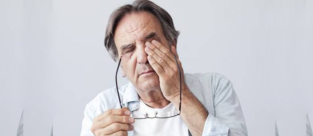 Man rubbing eyes after removing his glasses