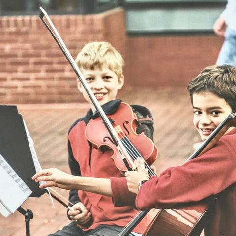 two young boys seated in front of music stands and holding violins and bow strings