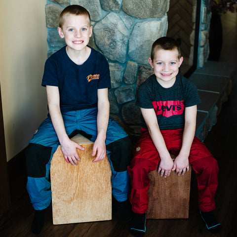 two elementary age brothers sitting on handmade cajon drums