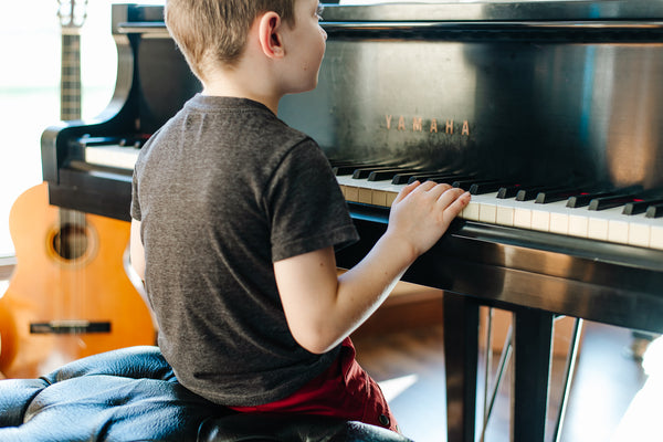 young boy in a grey tshirt and red pants sitting on a piano bench with his hands resting on the piano keys