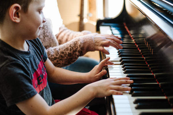 young boy in a grey tshirt playing a piano next to his mother