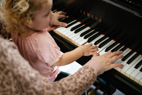 mom and daughter sitting and playing the piano together