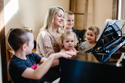 mother and her four children gathered around a piano and singing together