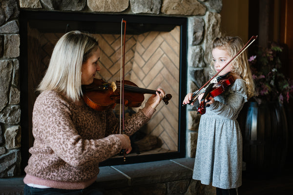 young girl with blond ringlets holding a violin next to a blond woman also holding a violin