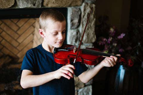 young boy holding a violin