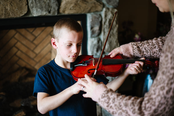 young boy wearing a navy blue shirt holding a violin while his mother's hands reach over to reposition his hands