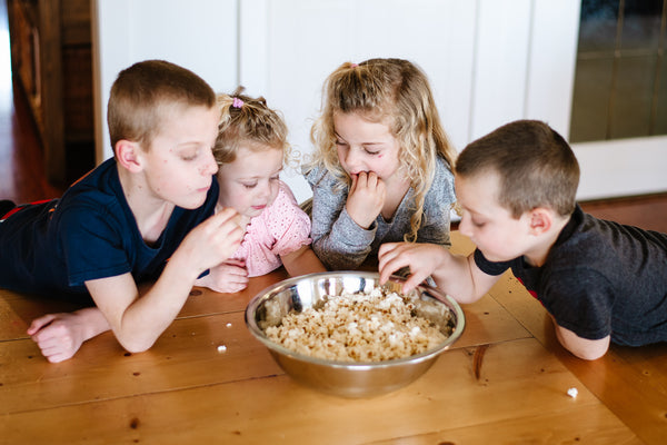 two brothers and two sisters sitting at a wood table eating fresh buttered popcorn out of a big silver bowl