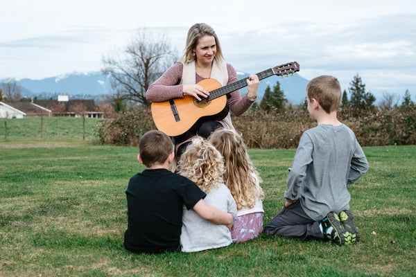 woman playing a guitar outside for a small group of children