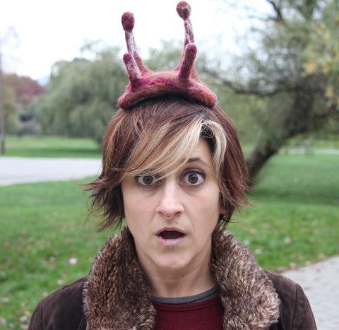 Woman with short hair with blond streaks wearing a maroon Needle felted slug headpiece for Halloween