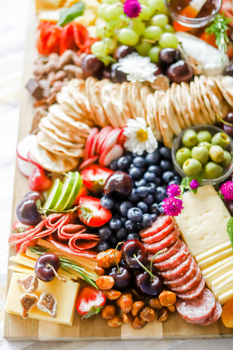 a meat and cheese board on acacia wooden cutting board, including crackers, blueberries, olives, salamis, cherries, dried figs, crackers, grapes