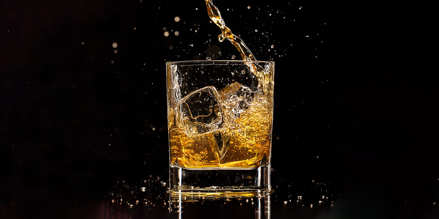 Whiskey pouring into cubic glass