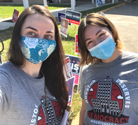 "Image: Two people wearing masks and grey ""Houston Deserves Democracy"" shirts while canvassing the polls on Election Day"