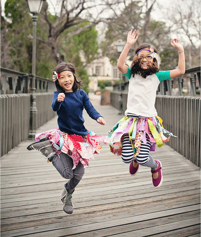 little girls each wearing a red and green scrap fabric tutu skirt for toddlers