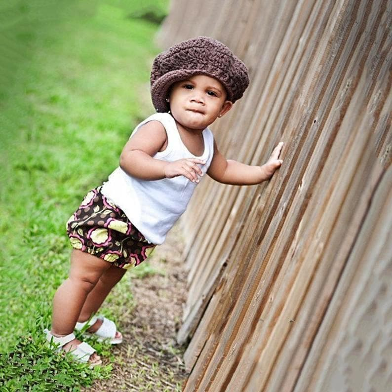 Baby girl wearing a brown newsboy hat for baby or toddler