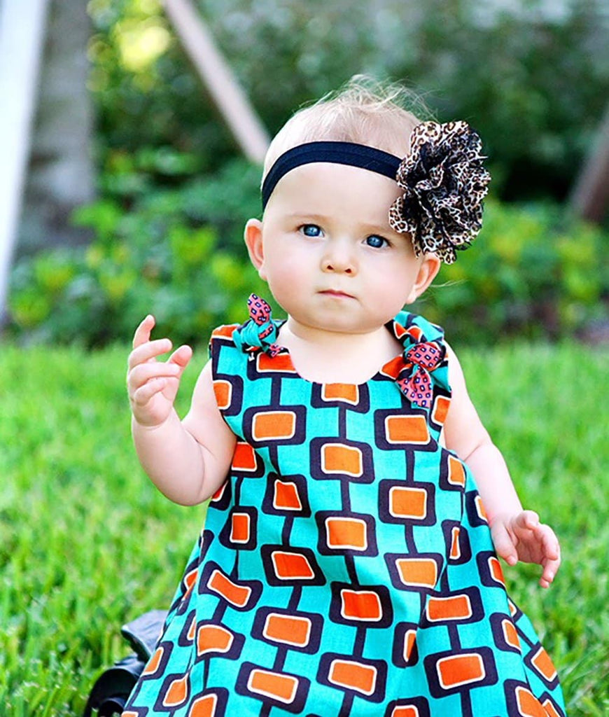 baby gear in a dress with green and orange retro print
