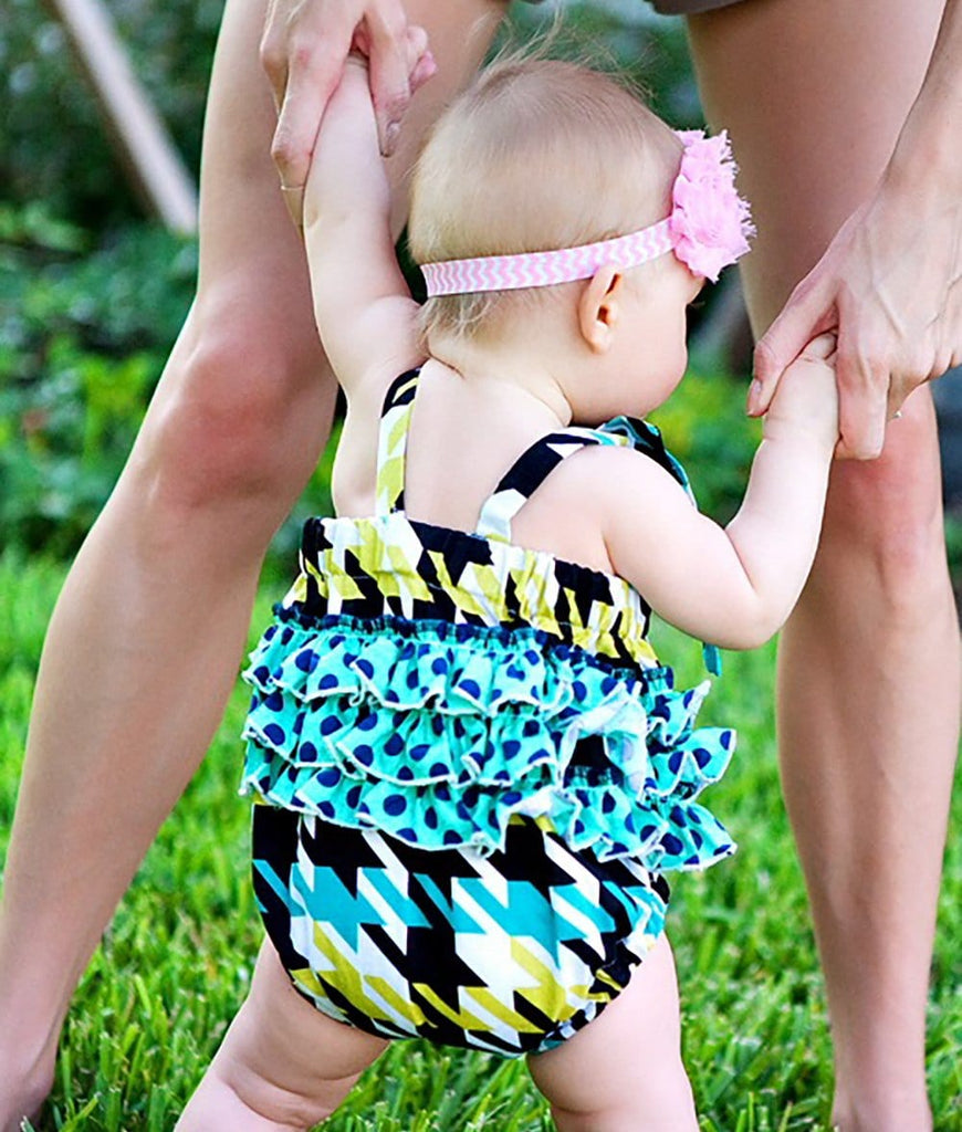 baby girl wearing a one piece romper with ruffles
