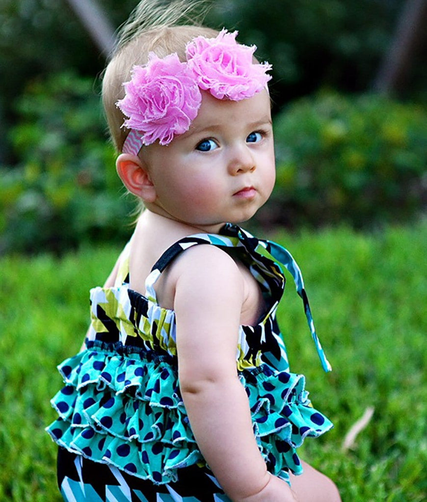 little girl wearing a baby romper with green polka dot print ruffles