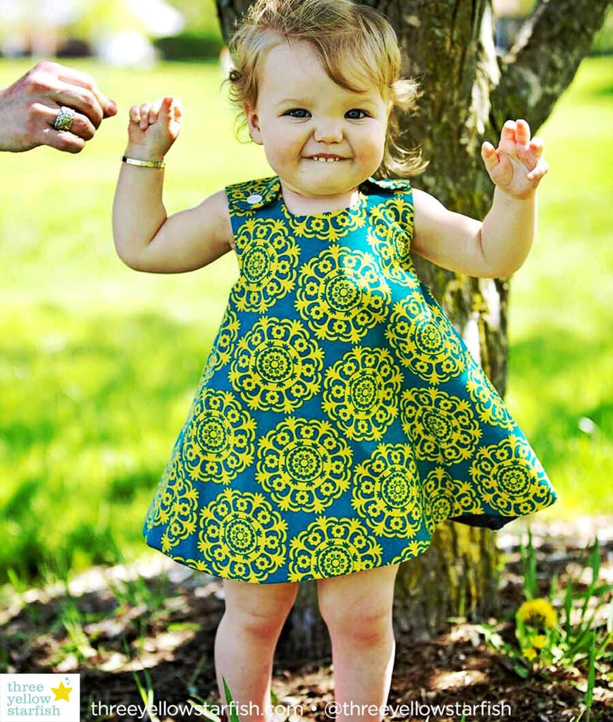 toddler girl wearing a mustard yellow and turquoise dress for girls