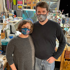 a man and pregnant woman standing together with masks on in a jewelry workshop